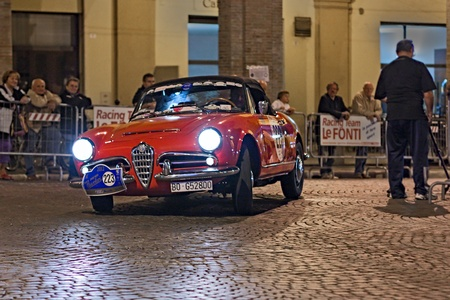 regularity: old car Alfa Romeo Giulia Spider (1963) runs at night in rally Gran Premio Nuvolari 2012, endurance race for classic cars, on September 21, 2012 in Meldola (FC), Italy