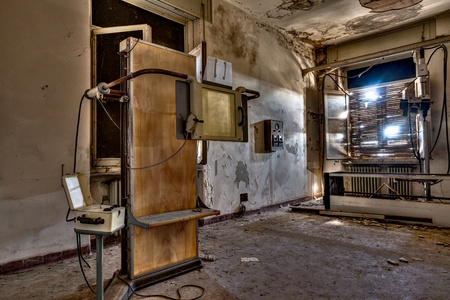 radiological: room of an abandoned hospital with old radiological equipment - desolate x-ray room in ruins Stock Photo