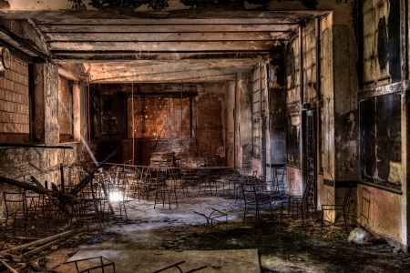 forsaken: interior of an abandoned building with old chairs, lit by a ray of light - desolate and sad hall with the windows bricked
