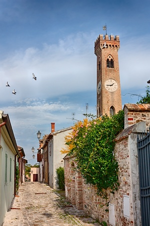 emilia romagna: narrow alley in the ancient italian town Santarcangelo di Romagna, with the antique clock tower on background