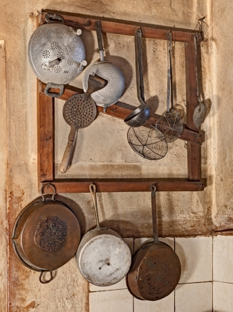 the old times: kitchenware hanging in the kitchen of an old country house  - retro equipment of old times Stock Photo