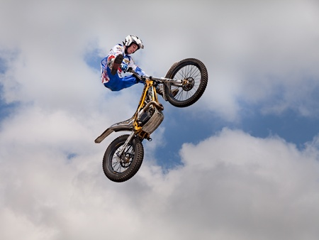 a stunt biker make an acrobatic jump at the trial and motocross freestyle show, during the motorcycle rally