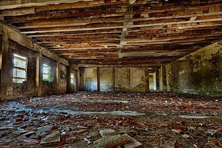 abandoned building interior with rubble and debris - desolate hall of an old destroyed factory photo