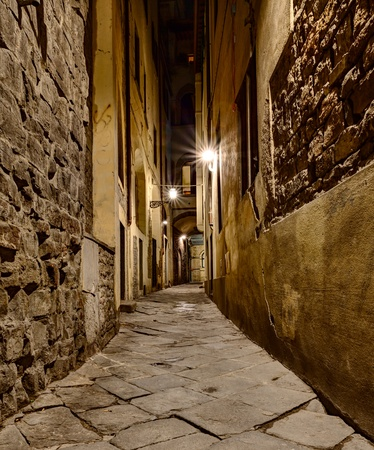 dark narrow alley at night lit by old street lamps in Florence, Tuscany, Italy