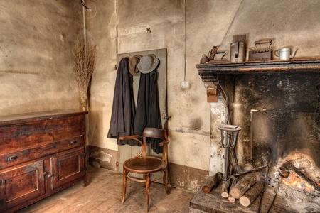 old times: tiempos antigua granja - interior de una vieja casa de campo con chimenea, armario de la cocina, mantas antiguas y escoba de paja Foto de archivo