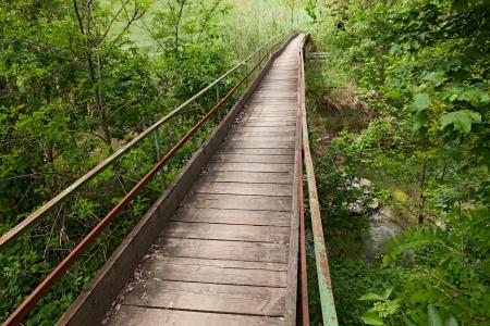 old narrow wooden bridge crossing the river in Emilia Romagna, Italy