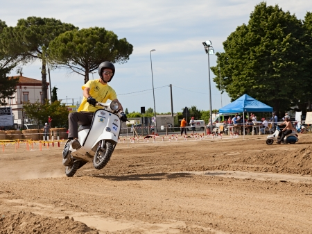 scrambler: Vespa cross: a driver makes a wheelie on the motocross track riding a vintage italian scooter during the motor festival Festa de mutor on June 9, 2013 in Pezzolo di Russi, RA, Italy