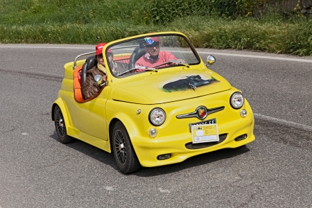 a yellow vintage tuned car Fiat 500 Abarth roadster running in rally for classic cars Raduno colline di cristallo on May 1, 2013 in Borgo Rivola, RA, Italy