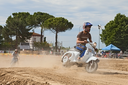 Vespa cross: a driver runs fast in the motocross track leaving a trail of dust riding a vintage italian scooter during the motor festival Festa de mutor on June 9, 2013 in Pezzolo di Russi, RA, Italy