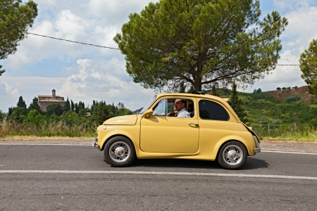 vintage tuned car Fiat 500 runs on the italian hills during the rally Raduno auto e moto depoca on July 7, 2013 in Fognano, RA, Italy