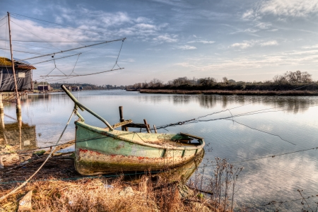 landscape at morning with abandoned boat and fishing shacks in the river of Ravenna, Italy