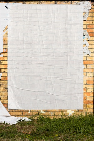 out in town: brick wall with blank poster and torn posters  Stock Photo