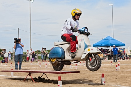 scrambler: a driver engaged in gymkhana race riding a vintage italian scooter Vespa during the motor festival Festa de mutor on June 9, 2013 in Pezzolo di Russi, RA, Italy