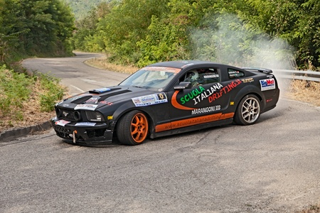 swerve: a drift racing car Ford Mustang in action with smoking tires in hairpin bend at Rally della Romagna 2013, on July 28, 2013 in Dovadola, FC, Italy Editorial