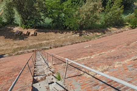 inclined: very steep staircase, dangerous descent from an high inclined brick wall