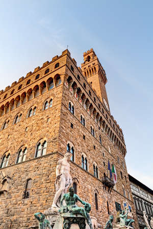 crenellated tower: a romanesque fortress palace Palazzo Vecchio, the town hall of Florence, Italy  and the antique statue of Neptune Stock Photo