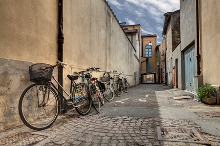 decadent: italian narrow street in the decadent old town - bicycles in a grunge dark alley in Italy