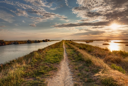 comacchio: panorama at sunset of the wetland, a long straight path across the lagoon in the natural reserve  Valli di Comacchio  in Italy