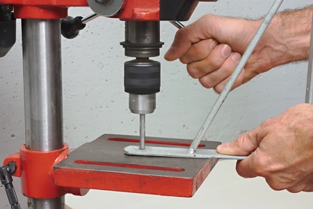 a worker drills a hole in iron bracket with a bench drill photo