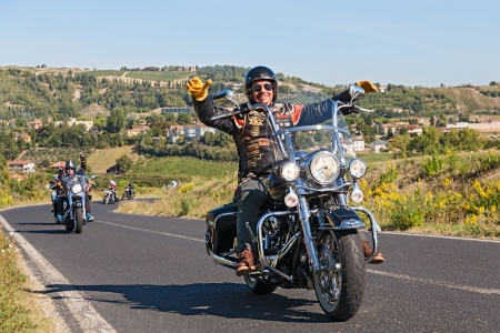 'cycles: a happy driver leads a group of bikers riding Harley Davidson at motorcycle rally Sangiovese tour by Ravenna Chapter on September 22, 2013 in Riolo Terme (RA) Italy