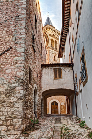 old narrow alley with view of the church tower in the antique italian town Trevi, Umbria, Italy,