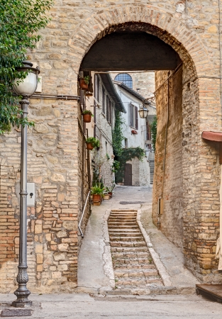 italian village: narrow alley with archway in the ancient town Bevagna, Umbtia, Italy
