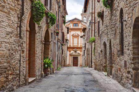 vintage: oude kerk aan het eind van een smal steegje in het middeleeuwse stadje Bevagna Umbrië, Italië Stockfoto