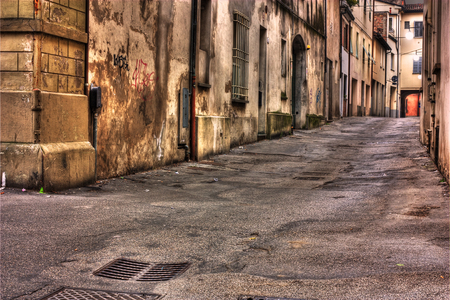street corner: grunge dark alley, slums of the city, squalid dirty corner of street, the decadent old town, street at night in the slum, urban decay in Italy, grunge distressed italian alleyway Editorial
