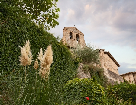bevagna: flowerbed, wall with creepers and tower bell of catholic church seen from below in Bevagna, Umbria, Italy