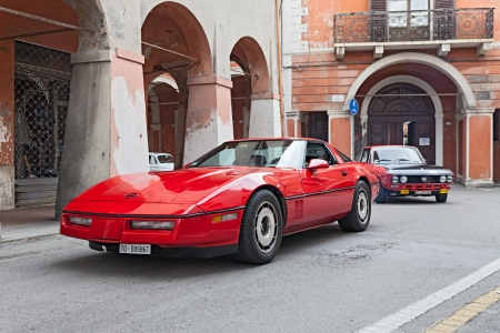 a vintage sportscar Chevrolet Corvette C4 runs along the city during the classic car rally Meeting Fiat 500 e auto depoca on November 10, 2013 in Bagnacavallo, RA, Italy