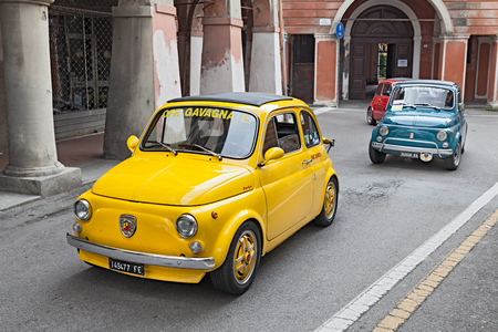 yellow vintage car Fiat 500 Abarth runs along the city during the rally Meeting Fiat 500 on November 10, 2013 in Bagnacavallo, RA, Italy