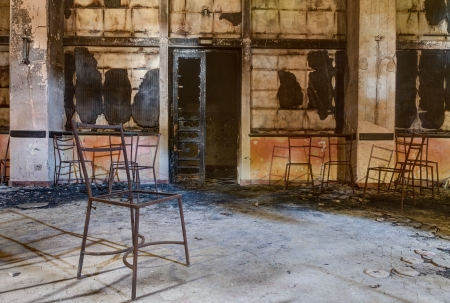 forsaken: interior of an abandoned building with old chairs - desolate and sad hall Stock Photo