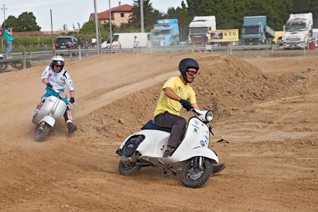 scrambler: Vespa cross: a motocross riders engaged in curve on the motocross track riding a vintage italian scooter during the motor festival Festa de mutor on June 9, 2013 in Pezzolo di Russi, RA, Italy