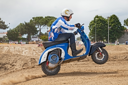 motosport: Vespa cross: a driver makes a wheelie on the motocross track riding a vintage italian scooter during the motor festival Festa de mutor on June 9, 2013 in Pezzolo di Russi, RA, Italy