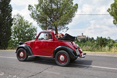 an old italian car Fiat 500 Topolino Trasformabile runs on the italian hills during the rally  Raduno auto e moto d