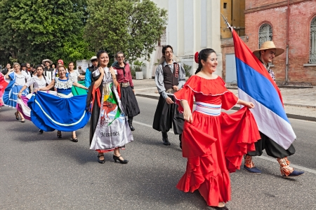 street parade of folk ensemble Raices Nuevas from El Alcazar, Misiones, Argentina - dancers in traditional dress performs popular dance during the International Folk Festival on August 4, 2013 in Russi, RA, Italy