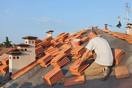 tar paper: roofing  construction worker on a roof covering it with tiles - roof renovation  installation of tar paper, new tiles and chimney