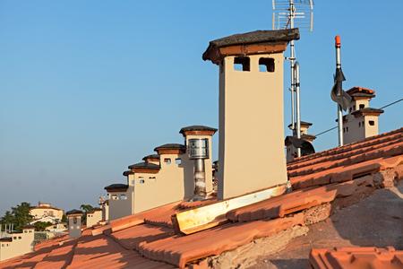 trussing: fila di camini sul tetto di un edificio - ristrutturazione installazione sul tetto di nuove tegole e camini Archivio Fotografico