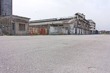 desolated street on the docks of port - desert suburbs of the city with abandoned warehouses and factories Stock Photo