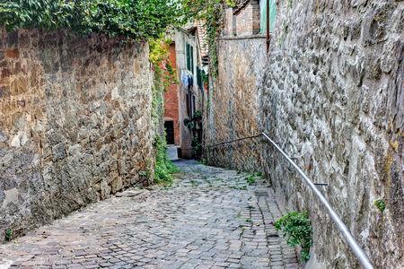 oude smalle steegje in Toscaanse dorp - antieke italiaanse rijstrook in Montalcino, Toscane, Italië
