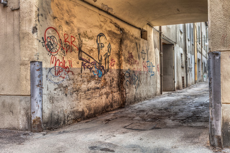street corner: narrow alley in the old town - corner of a decadent city street and grunge wall with graffiti - draw of smoker of hashish - drug addiction, marijuana, cannabis, joint, reefer, spliff Stock Photo