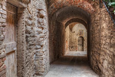vintage: oude smalle steegje met poort in het middeleeuwse Italiaanse stadje Todi, Umbrië, Italië - verkorting van een pittoresk donkere stad hoek Stockfoto