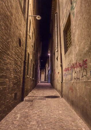 narrow dark alley in the old town - distressed alleyway in the italian city - grunge aged street at night   Stock Photo