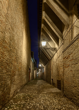 narrow dark alley in the Italian old town - street at night with cobbled paving in a medieval city of Italy photo