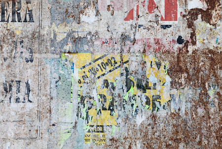 grunge ripped poster background - texture of torn advertisement on an old rusty billboard panel photo