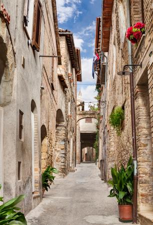 vintage: pittoreske smalle steegje met oude boog, onderdoorgang, planten en bloemen in Bevagna, Umbrië, Italië Stockfoto