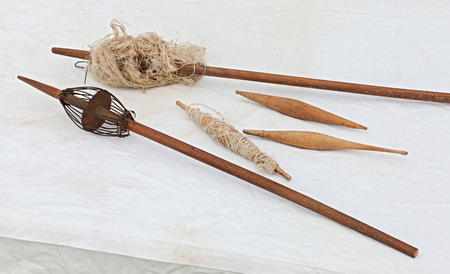 spinning wheel: ancient distaff and spindle, tools for manual spinning thread of wool, flax, hemp and other natural textile fiber