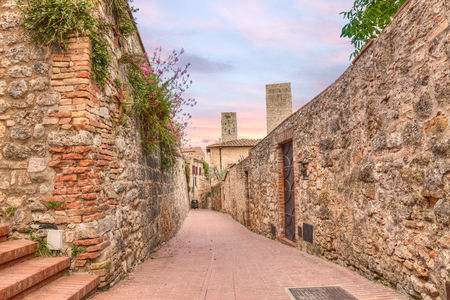 narrow alley in San Gimignano, Tuscany, Italy - picturesque ancient alleyway in tuscan medieval town  photo