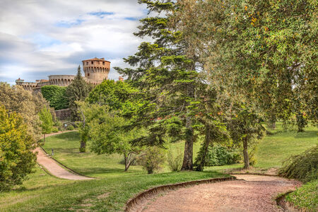 volterra: landscape of park with pathway and a medieval castle in Volterra, Tuscany, Italy