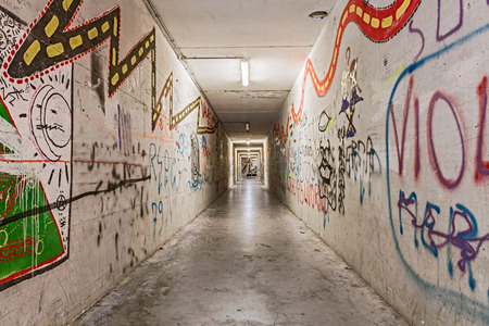urban underground tunnel with graffiti - light and shadows on grunge pedestrian underpass - dark narrow subway alley photo